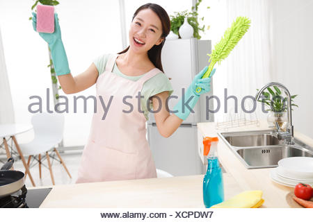 Young woman cleaning in Kitchen - Stock Photo