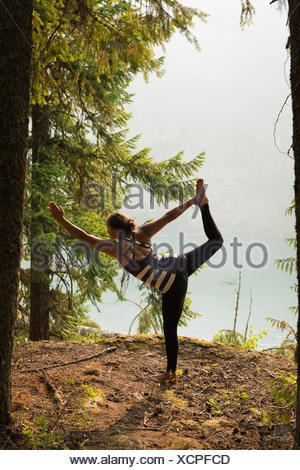 Fit woman performing stretching exercise in a lush green forest - Stock Photo