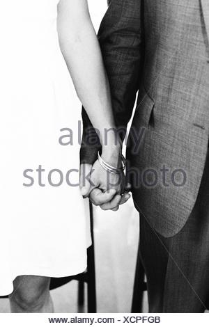 Midsection Of Couple Holding Hand Of Each Other - Stock Photo