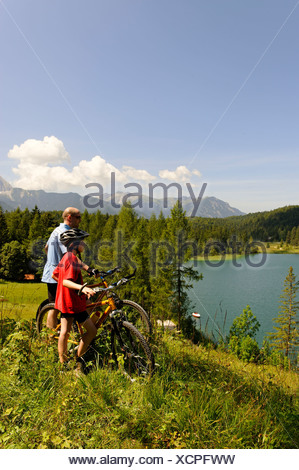 Cycling tour with mountain bikes, father and son in front of Lake Lautersee, Mittenwald, Karwendel Mountains, Werdenfelser Land - Stock Photo