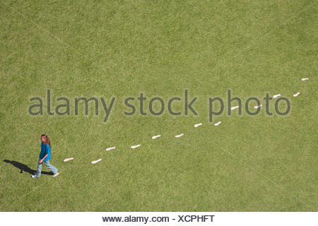Young girl walking leaving trail of footprints - Stock Photo