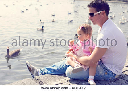 Iceland, Father and daughter (12-17months) sitting by lake with swimming ducks - Stock Photo