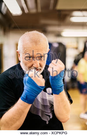 Senior man with his fists raised at boxing training - Stock Photo