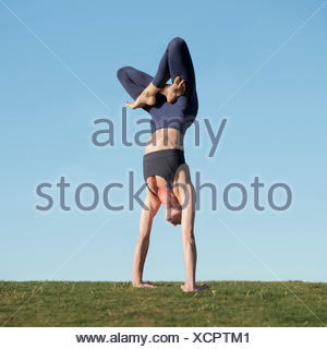 Young woman, outdoors, in yoga position - Stock Photo