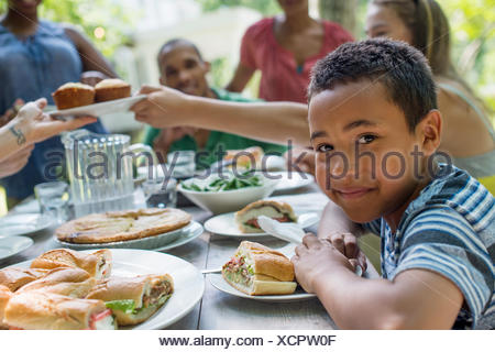 A family gathering, men, women and children around a table in a garden in summer. A boy smiling in the foreground. - Stock Photo