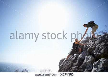 Rock Climbing Couple Ascending Rock In Bright Sunlight Man