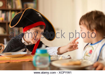 Boy dressed in pirate costume playing with toddler brother - Stock Photo