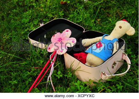 Suitcase with teddy bear and wand - Stock Photo
