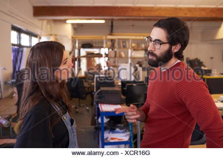 Two Designers Having Informal Meeting In Modern Office - Stock Photo