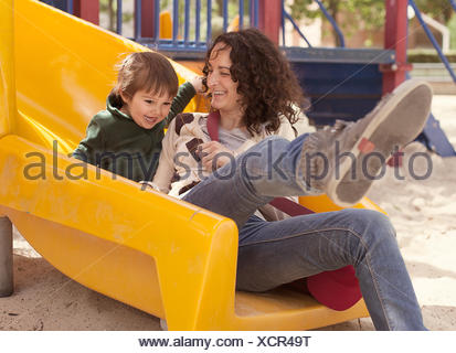Mother and son on a slide in playground - Stock Photo