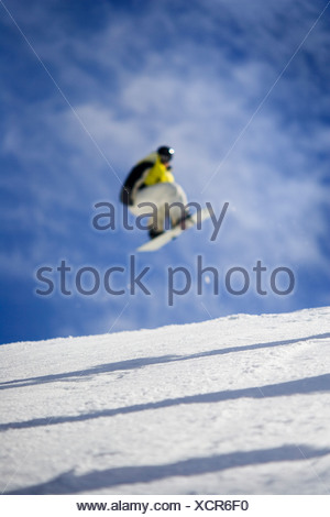 Male freestyle snowboarder grabs his board off a jump. - Stock Photo