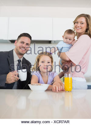 Family at breakfast table in house - Stock Photo