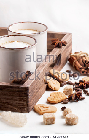 Two cups of cappuccino served with spices and cookies as hearts on white textile. - Stock Photo