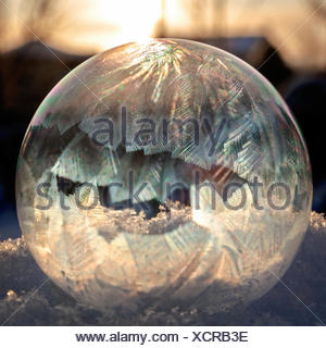 A soap bubble freezing in sun - Stock Photo