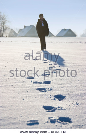 Germany, Vechelde, Boy walking in snow with footprints in foreground - Stock Photo