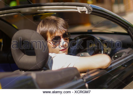 Teenage boy sitting in a convertible car - Stock Photo