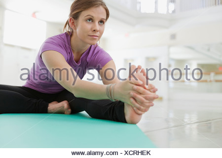 Woman stretching in yoga studio - Stock Photo