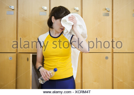 Woman wiping sweat in locker room - Stock Photo