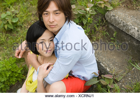 Young couple sitting on steps - Stock Photo