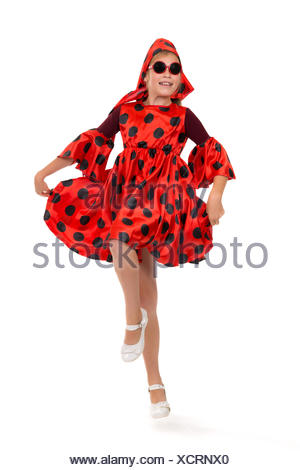 teen girl dancing in a red polka-dot dress with sunglasses - Stock Photo