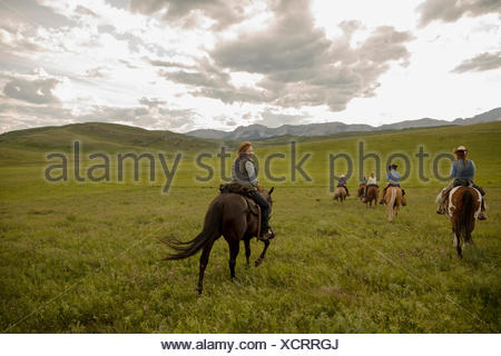Female ranchers riding horses in remote field - Stock Photo