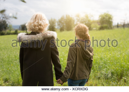 Rear view of mother and teenage daughter holding hands - Stock Photo