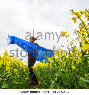 Woman holding wide blue scarf spinning in rapeseed field - Stock Photo