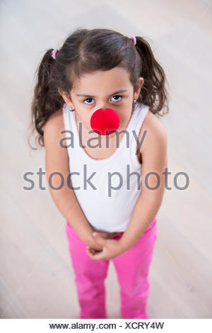 Portrait of cute little girl wearing clown nose at home - Stock Photo