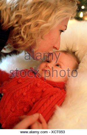 Woman kissing child, Christmas baby, newborn baby love - Stock Photo
