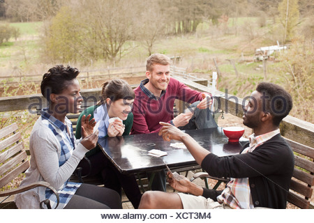 Two couples playing cards, outdoors - Stock Photo