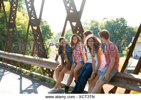 Group of friends sitting on bridge - Stock Photo