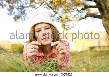 Portrait of teenage girl lying on grass - Stock Photo