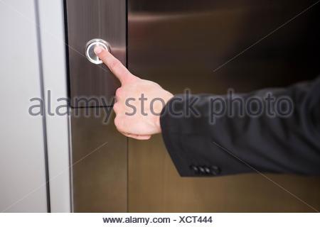 Businessman pressing elevator button - Stock Photo