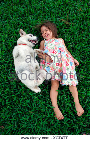 Girl and her dog playing in the grass. - Stock Photo