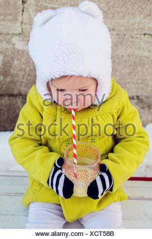 Girl sitting outside drinking through a straw - Stock Photo