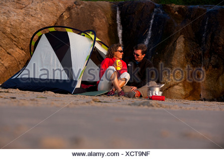 Male and female couple laughing while cooking in front of their tent at sunset on the beach. - Stock Photo