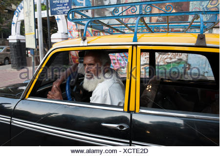A bearded Indian taxi driver looks out of his cab's window. - Stock Photo