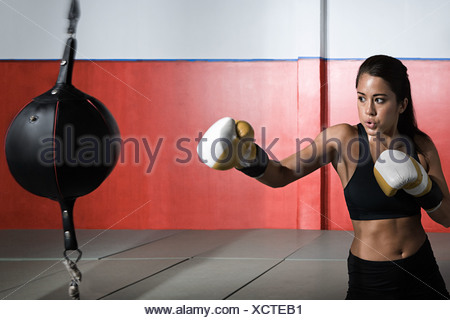 Female boxer with punch bag - Stock Photo