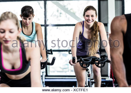 Fit women working out at spinning class - Stock Photo