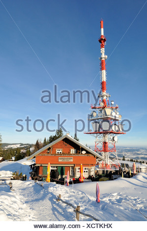 The 95 meter high transmission mast of the broadcaster ORF on the 1064 meter high Pfaender Peak with the guest house - Stock Photo