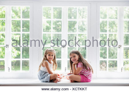 Two girls playing, sharing a digital tablet. - Stock Photo