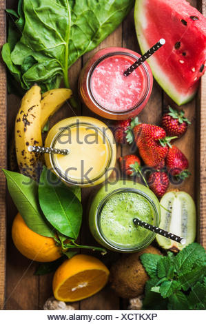 Fresh blended smoothies in glass jars with straws on wooden baclground served with watermelon, kiwi, orange, banana, strawberry, - Stock Photo