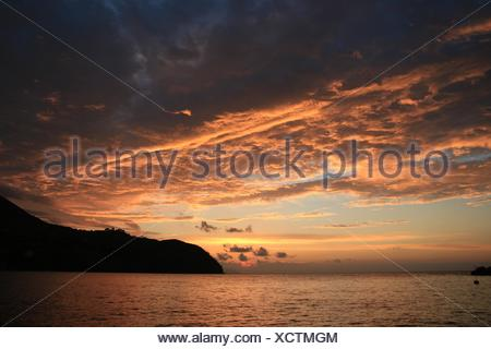 Scenic View Of Sea And Silhouette Mountains Against Cloudy Sky During Sunset - Stock Photo
