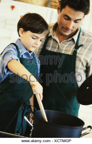 Boy cooking with his father - Stock Photo