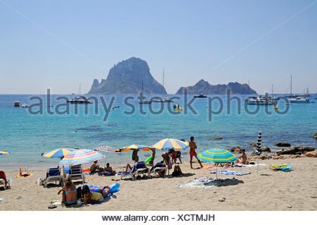 Holidaymakers on Cala d'Hort beach with Isla Vedra island, Ibiza, Pityuses, Balearic Islands, Spain, Europe - Stock Photo