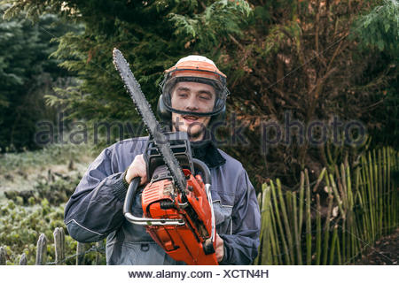 Portrait of professional gardener with chainsaw standing in the garden. - Stock Photo
