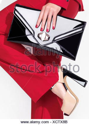 Woman wearing a red suit and high heel shoes holding a clutch handbag - Stock Photo