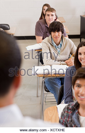Male high school teacher and students in classroom - Stock Photo