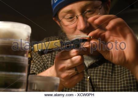 Man tying a fishing fly in Seattle, Washington, USA - Stock Photo