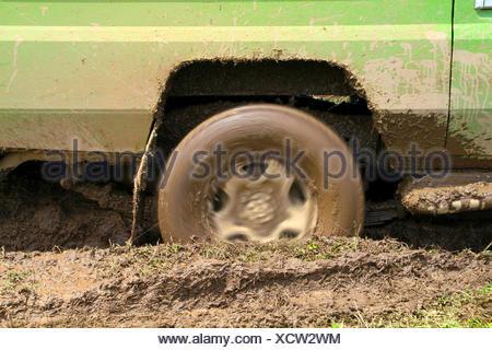 spinning wheel of a safari car sticking in the mud, Tanzania, Serengeti National Park - Stock Photo